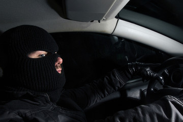 masked man sitting in a car