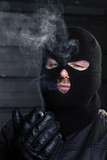 masked man smoking a cigarette