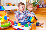 Fototapety two cute baby toddlers playing in nursery room