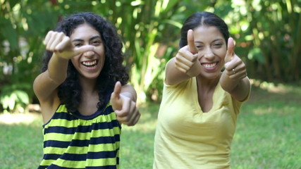 Two young women giving thumbs up.