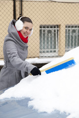 Cute young woman removing snow from car windshield