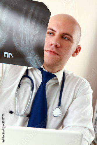 A male doctor studying a x-ray image,