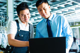 Worker and supervisor with laptop in a factory poster
