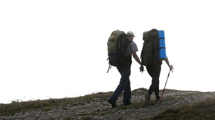 Young couple with backpacks traveling on the misty road