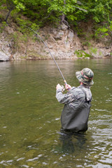 Fisherman pulls caught salmon