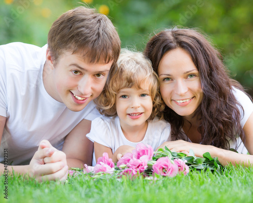 Happy family lying on green grass