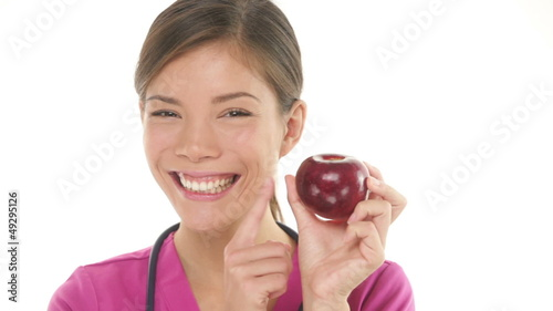 Medical doctor nurse woman showing and eating apple