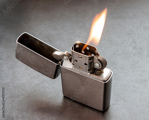 Silver metal lighter on black background with flame.