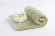 A green towel rolled up with flower on a white background