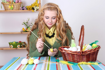 young attractive blond painting easter eggs