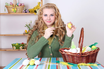 young attractive woman painting easter eggs
