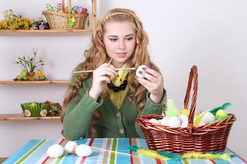 beautiful teenage girl painting easter eggs