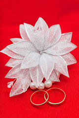 Flower and two wedding rings on a red background