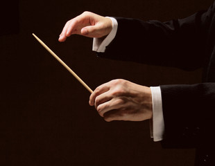 Concert conductor's hands with a baton isolated
