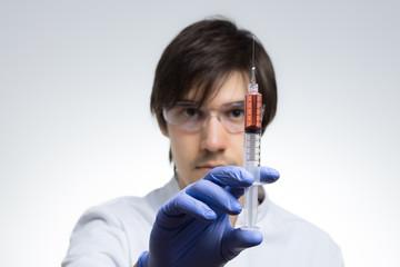 Junger Wissenschaftler hält Spritze mit roter Flüssigkeit