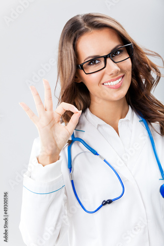 Female doctor with okay gesture, over grey