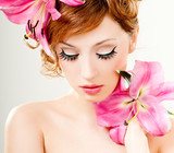 beautiful girl with pink lilies in her hair