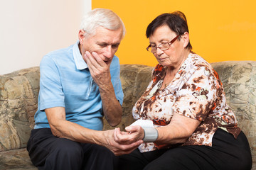 Worried seniors measuring blood pressure