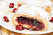 Cherry strudel with powdered sugar and almonds