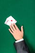 Hand with aces on the green table. Addiction to the gambling