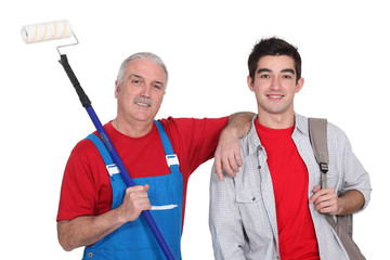 mature painter holding roller with young apprentice