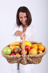 Woman holding basket of fruit