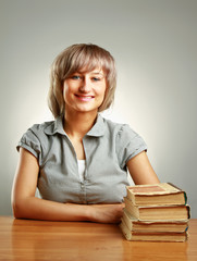 Smiling young woman sitting on the desk with