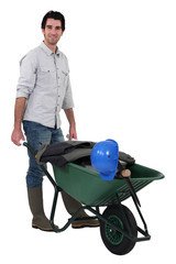 A construction worker with a wheelbarrow.
