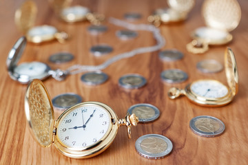 Group gold pocket watch against the euro coins.