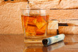 Glass of whiskey and cigar on brick wall background