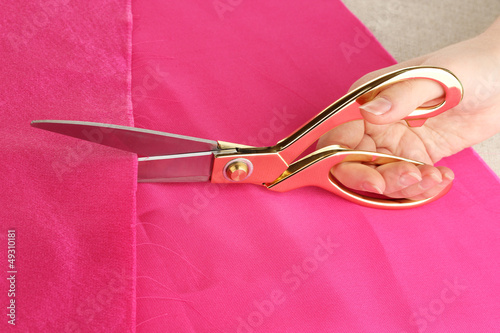 Seamstress cut pink fabric on beige fabric background