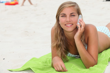 Teenage girl making a phone call on the beach