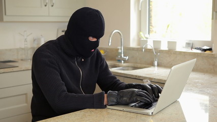 Burglar hacking into laptop