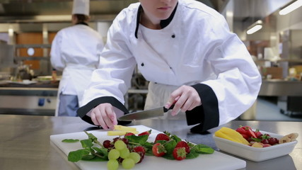 Cook slicing fruit on the counter
