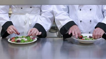 Two cooks preparing salads