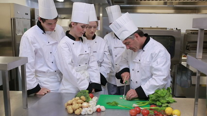 Cooks watching head chef slicing vegetables