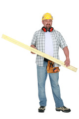 Tradesman carrying a plank of wood