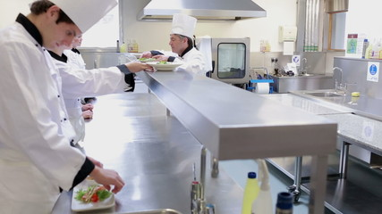 Cooks presenting their meals to the head chef