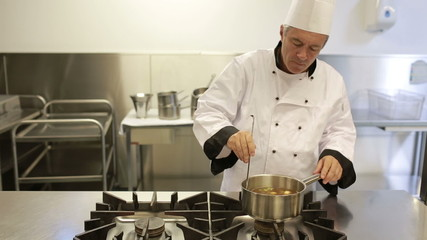 Cook testing soup in a kitchen