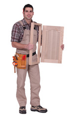 carpenter holding a wooden window frame