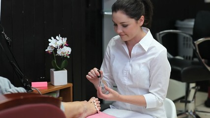 Beautician varnishing toenails