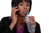 Businesswoman on the phone drinking from a bottle of water