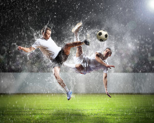 two football players striking the ball