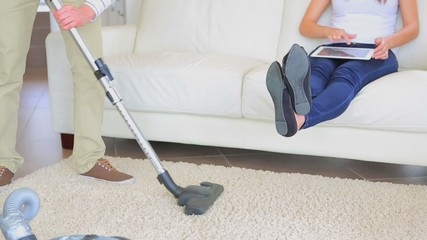 Man hoovering carpet while wife is relaxing on sofa
