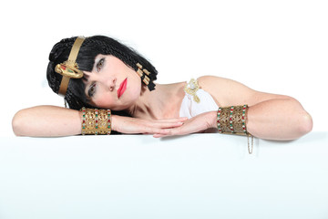 Woman dressed as Cleopatra leaning on a board for text
