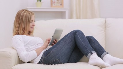 Cute woman touching her tablet and smiling