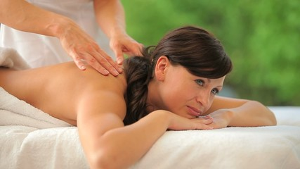 Joyful woman being massaged in a spa