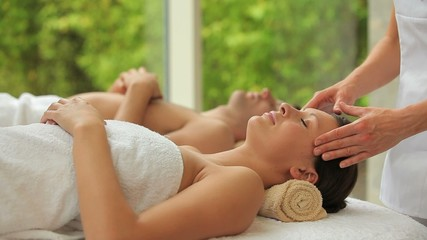 Couple being massaged in a spa center