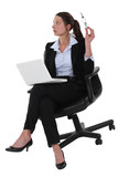 businesswoman sitting in a chair and working on her laptop