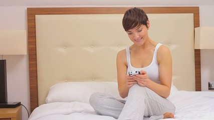Woman texting on her smartphone in her bed